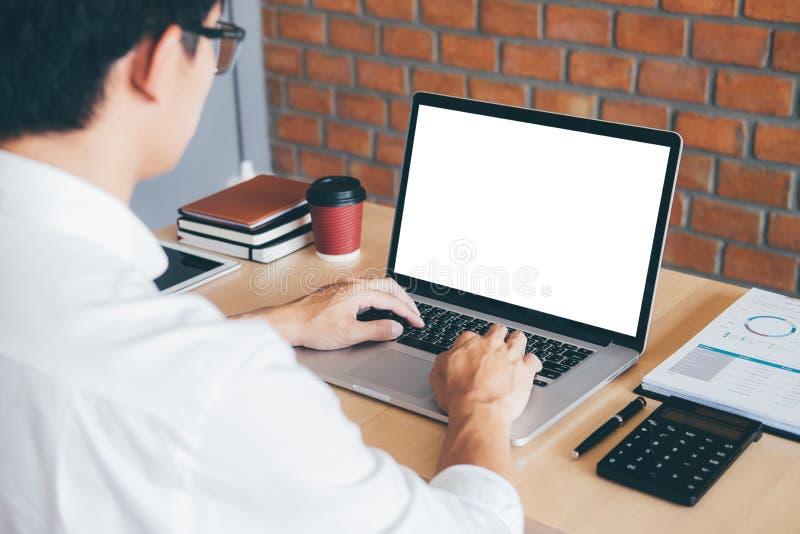 Imagen del hombre joven que trabaja delante del ordenador portátil que mira la pantalla con una pantalla blanca limpia y el espac foto de archivo libre de regalías