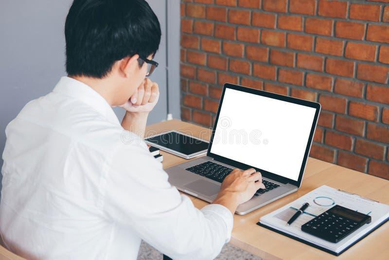 Imagen del hombre joven que trabaja delante del ordenador portátil que mira la pantalla con una pantalla blanca limpia y el espac foto de archivo