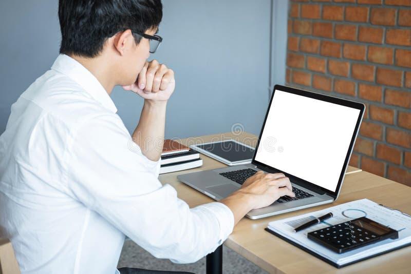 Imagen del hombre joven que trabaja delante del ordenador portátil que mira la pantalla con una pantalla blanca limpia y el espac fotografía de archivo