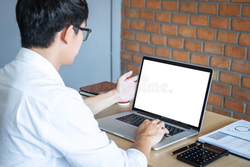 Imagen del hombre joven que trabaja delante del ordenador portátil que mira la pantalla con una pantalla blanca limpia y el espac imágenes de archivo libres de regalías