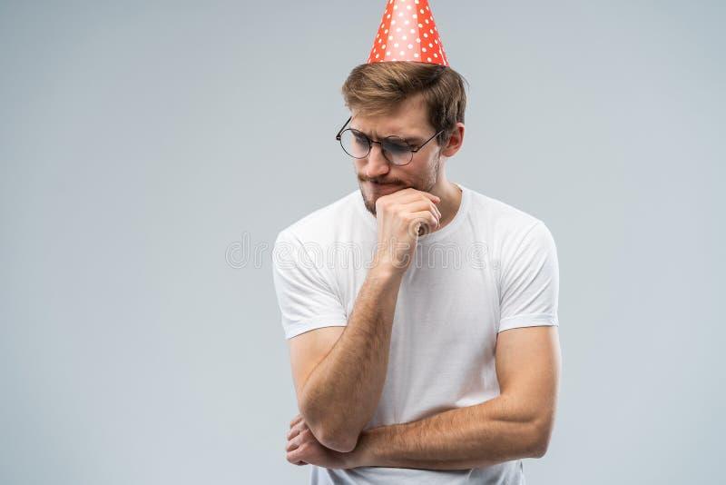Imagen del hombre joven subrayado infeliz que tiene mirada infeliz, sintiendo cansado y usado con las preparaciones de la fiesta  fotografía de archivo libre de regalías