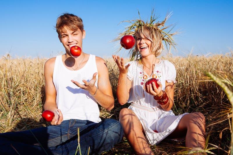 Imagen del hombre joven y de la mujer con las manzanas en campo de trigo fotos de archivo