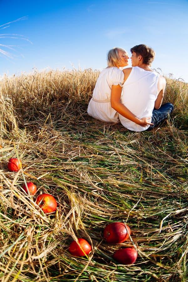 Imagen del hombre joven y de la mujer con las manzanas en campo de trigo imagen de archivo libre de regalías