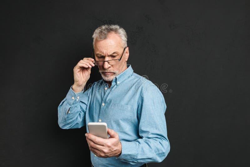 Imagen del hombre mayor maduro serio 60s con el pelo gris que mira o foto de archivo