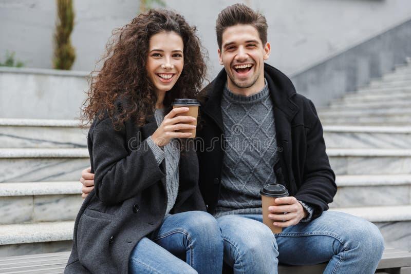 Imagen del hombre y de la mujer caucásicos 20s en ropa caliente, café para llevar de consumición de los pares mientras que se sie fotografía de archivo