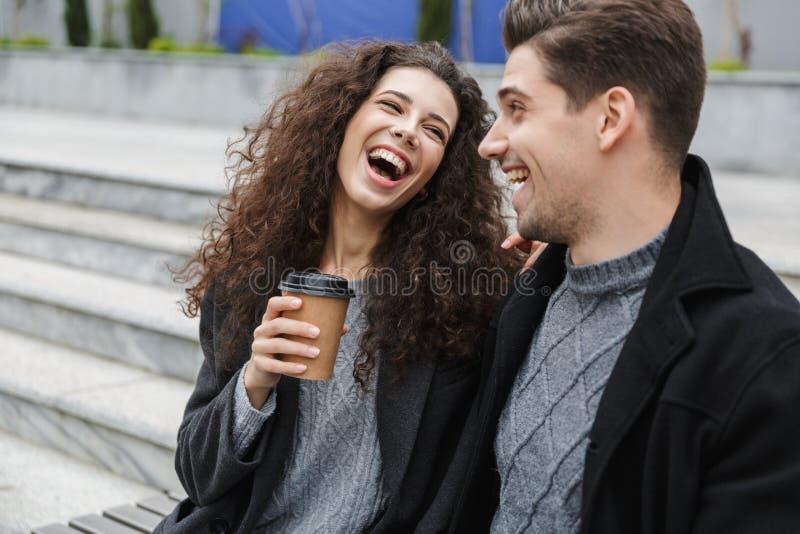 Imagen del hombre y de la mujer felices 20s en ropa caliente, café para llevar de consumición de los pares mientras que se sienta fotos de archivo