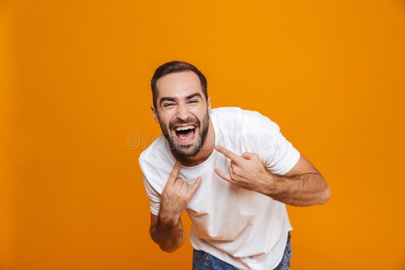 Imagen del individuo feliz 30s en la camiseta que disfruta y que muestra la situación del rato de la muestra de la roca, sobre fo imagen de archivo