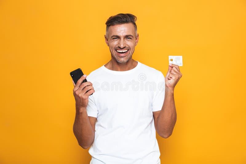 Imagen del individuo hermoso 30s en la camiseta blanca que sostiene el teléfono móvil y la tarjeta de crédito fotos de archivo