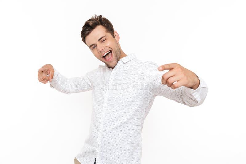 Imagen del individuo positivo 30s que ríe y que señala los fingeres en el camer imagen de archivo libre de regalías