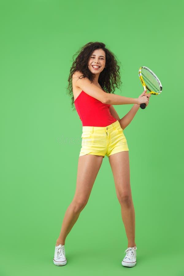 Imagen del jugador de tenis de sexo femenino moreno 20s que sonríe y que celebra la estafa fotos de archivo