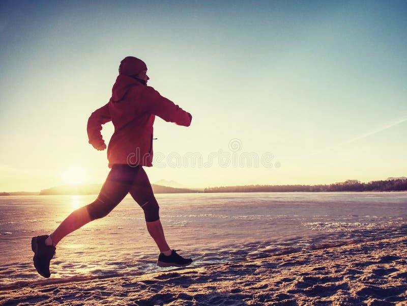 Imagen del lado de la mujer del atleta en funcionamiento de la playa en invierno fotos de archivo