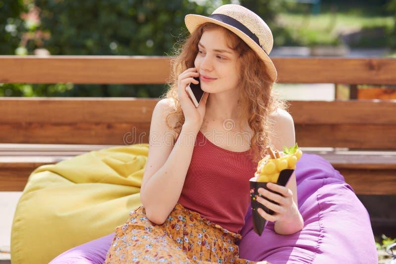 Imagen del modelo delgado encantado que presenta en los beanbags, hablando sobre el teléfono, teniendo conversación, mirando a un imagen de archivo