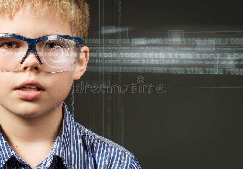 Imagen del muchacho lindo con los vidrios digitales. Concepto de la tecnología. imagen de archivo