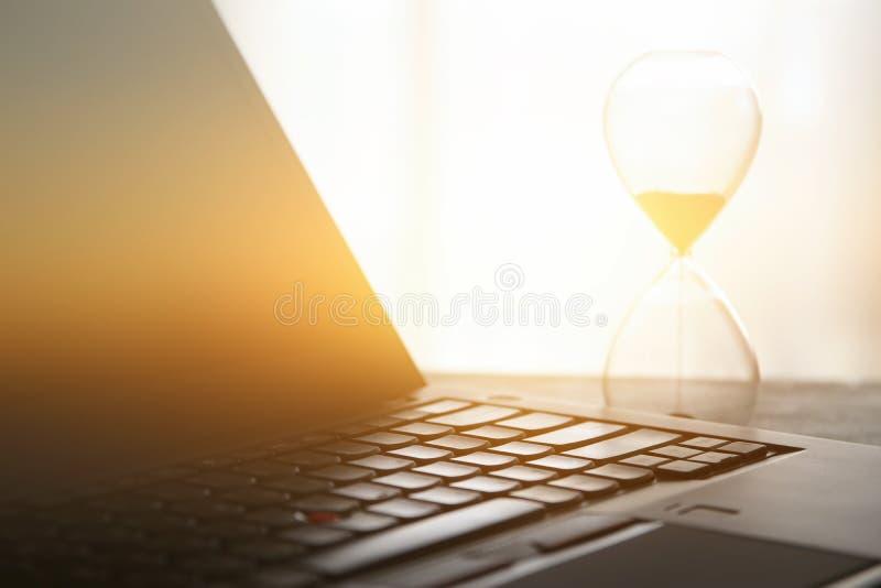 Imagen del ordenador portátil sobre el escritorio de madera en la oficina, lugar de trabajo u hogar y reloj de arena Vintage filt fotografía de archivo libre de regalías