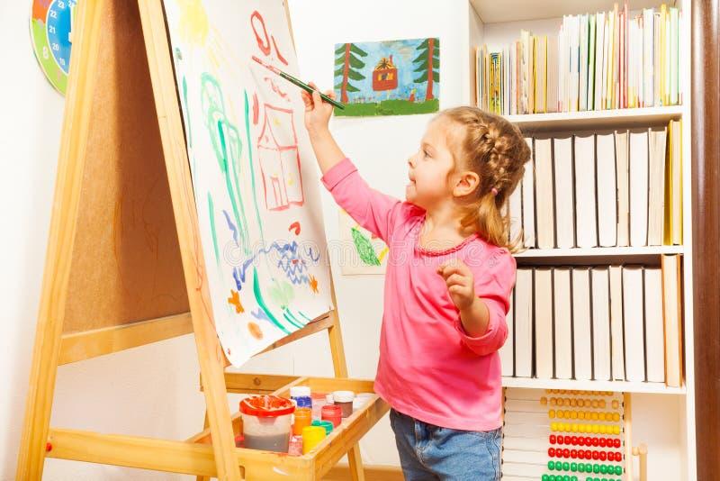 Imagen del paisaje de la pintura del niño en el caballete fotografía de archivo