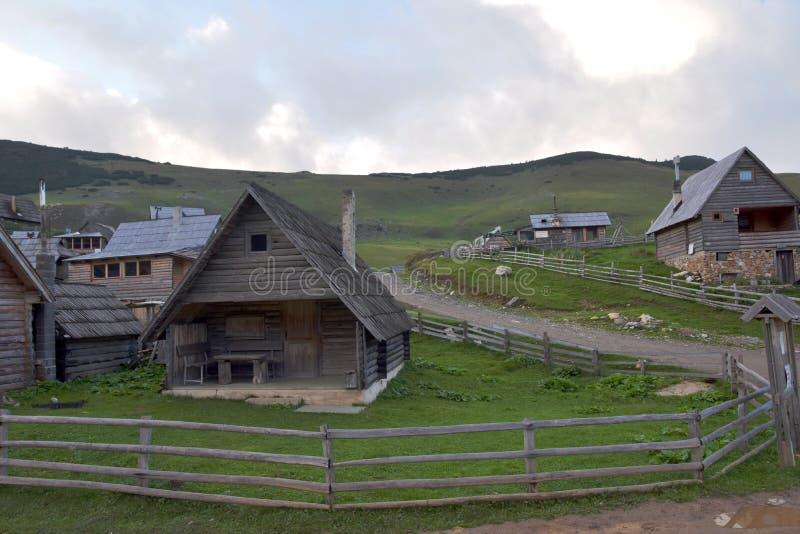 Imagen del paisaje de las chozas del pueblo del pastor de la montaña con la vista del bosque y del cielo azul en el fondo foto de archivo libre de regalías