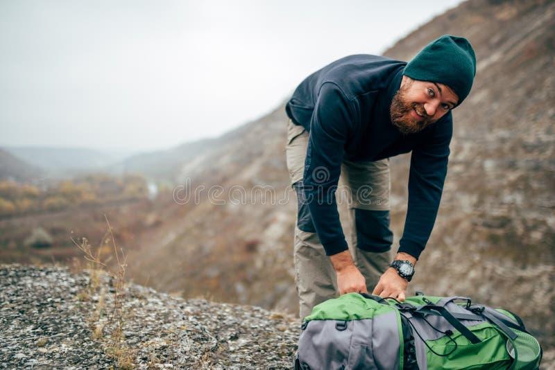 Imagen del paisaje del hombre joven del caminante que camina en montañas con la mochila del viaje Varón barbudo del viajero que p imagen de archivo
