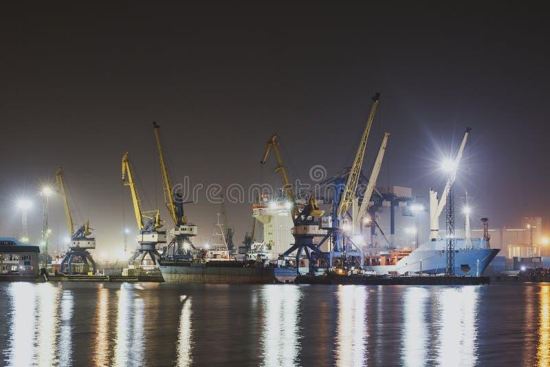 Imagen del panorama del puerto iluminado del cargo en Novorossiysk, Rusia en la noche con las terminales de contenedores, el buqu fotos de archivo