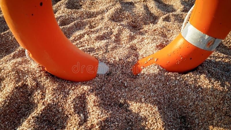 Imagen del primer del anillo de la salvaci?n de vidas para ayudar a la gente que se ahoga en el mar que est? situado en la playa  imagenes de archivo