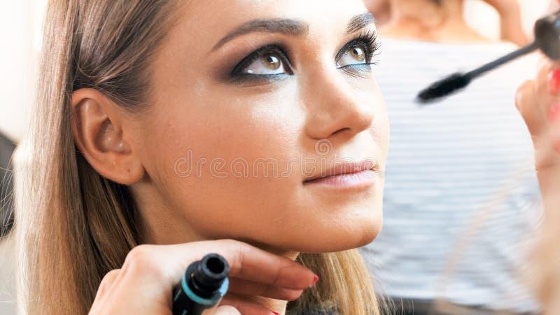 Imagen del primer del artista de maquillaje que aplica el rimel con el cepillo fotografía de archivo libre de regalías