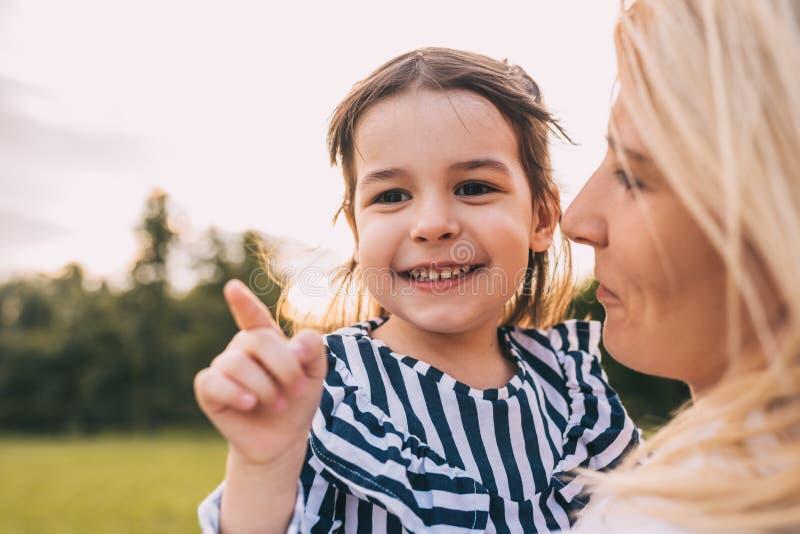 Imagen del primer de la hija linda feliz de la niña que abraza a su madre en el parque Madre e hija sonrientes de amor pasar tiem fotografía de archivo