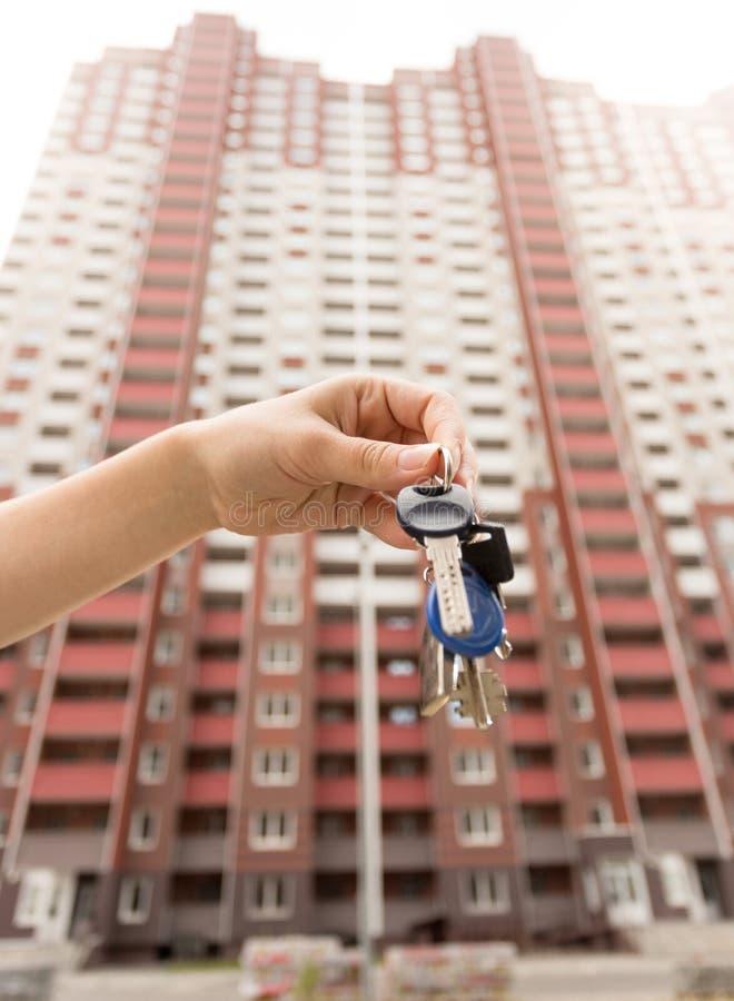 Imagen del primer de la mano femenina que lleva a cabo llaves del nuevo apartamento contra casa grande bajo construcción foto de archivo