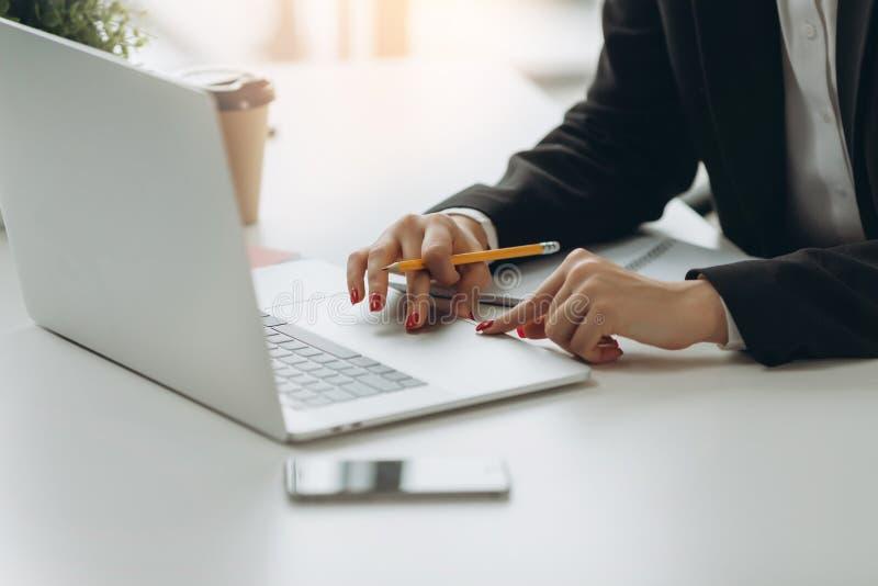 Imagen del primer de la mano usando y tocando en panel t?ctil del ordenador port?til en la tabla Trabajo en oficina moderna foto de archivo libre de regalías