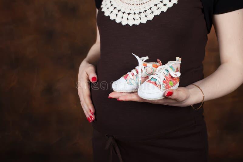 Imagen del primer de la mujer embarazada que toca su vientre con las manos fotos de archivo