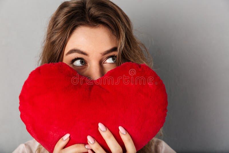 Imagen del primer de la mujer en la camiseta que oculta detrás de corazón de la alegría foto de archivo libre de regalías