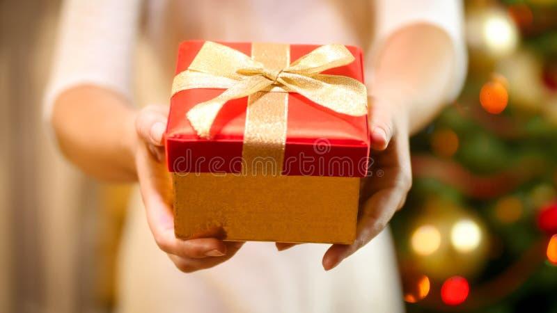 Imagen del primer de la mujer joven que muestra la caja de regalo de la Navidad con el arco de oro in camera fotos de archivo libres de regalías