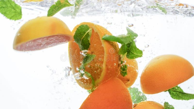 Imagen del primer de la naranja jugosa del corte fresco y porciones de hojas de menta que caen y que salpican en el agua clara co fotos de archivo