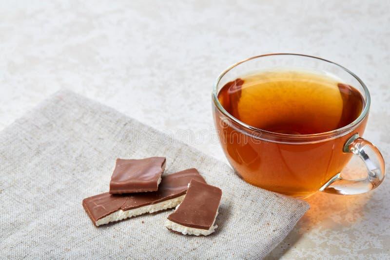 Imagen del primer de la visión superior del té en taza transparente con la servilleta del chocolate y del algodón en el fondo bla fotos de archivo