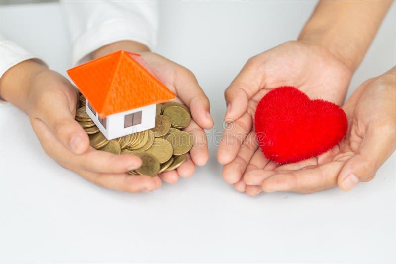 Imagen del primer de las manos femeninas que llevan a cabo la casa modelo y el corazón rojo Caridad, propiedades inmobiliarias y  foto de archivo