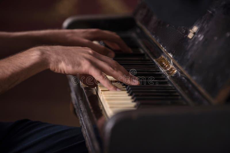 Imagen del primer de manos de un músico que juega encendido imagenes de archivo
