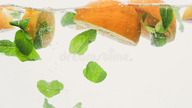 Imagen del primer de naranjas jugosas frescas cortadas con las hojas de menta que flotan en agua clara contra el fondo blanco fotografía de archivo