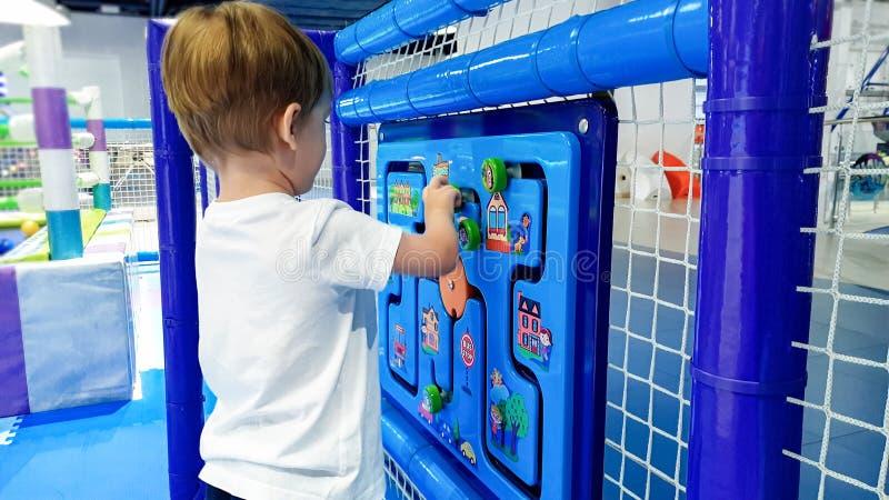 Imagen del primer de poco niño pequeño que soluciona rompecabezas en el palyground de los niños en el parque de atracciones Conce imágenes de archivo libres de regalías