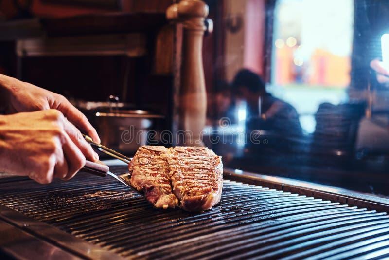 Imagen del primer de un filete delicioso de cocinar de la carne en una parrilla imagen de archivo
