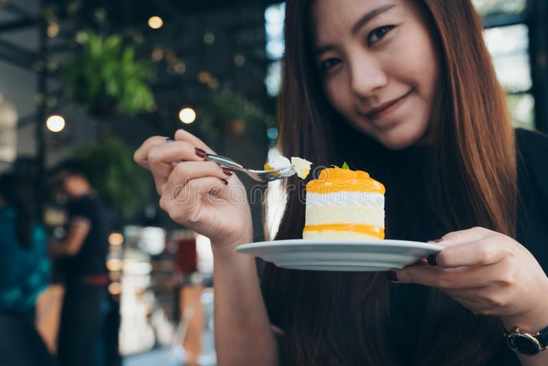 Imagen del primer de una mujer asiática hermosa que sostiene y que come una torta anaranjada imagen de archivo