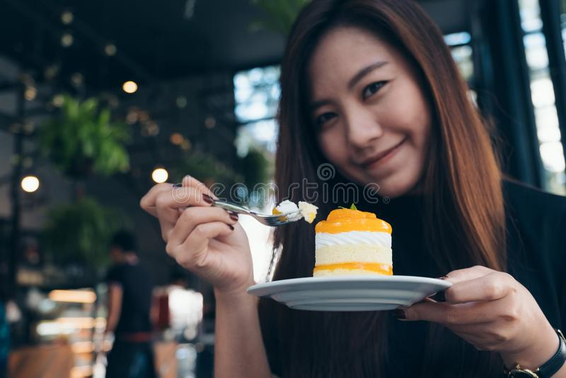 Imagen del primer de una mujer asiática hermosa que sostiene y que come una torta anaranjada fotografía de archivo