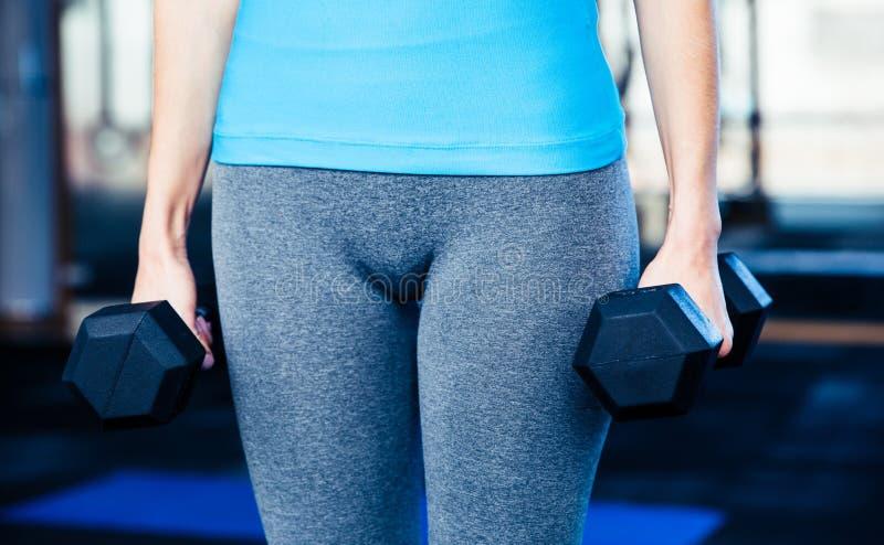 Imagen del primer de una mujer que se coloca con pesas de gimnasia imagen de archivo libre de regalías