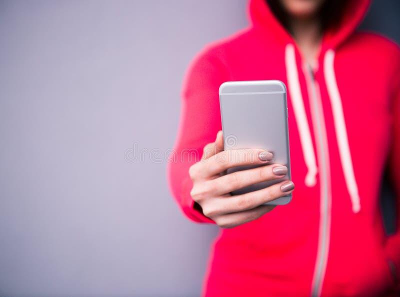 Imagen del primer de una mujer que sostiene smartphone imagen de archivo