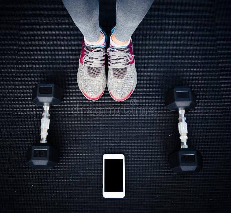 Imagen del primer del piernas femeninas en el gimnasio imagen de archivo libre de regalías