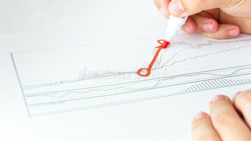 Imagen del primer del dibujo masculino de la mano que aumenta el gráfico financiero en el papel usando los datos comunes de las v imagen de archivo