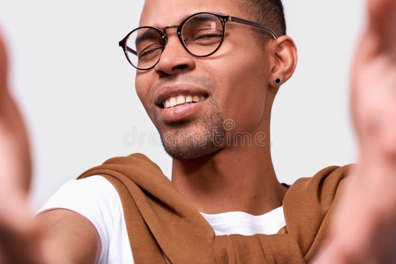 Imagen del primer del hombre joven afroamericano hermoso gafas que sonríe, el llevar, mirando la cámara y tomando el autorretrato fotos de archivo