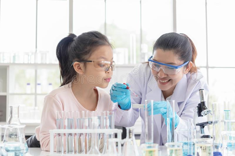 Imagen del profesor de la mujer y de la estudiante en clase de la ciencia del laboratorio Chica joven emocionada en clase del lab foto de archivo libre de regalías