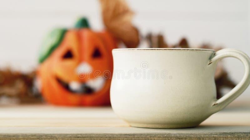 Imagen del pumpkie borroso sobre fondo de madera con la taza de te foto de archivo