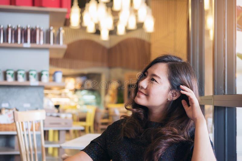 Imagen del retrato de una mujer asiática hermosa sonriente con sentirse bien sentarse y la relajación en café moderno fotografía de archivo