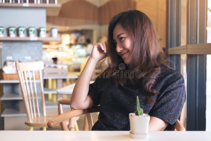 Imagen del retrato del primer de una mujer asiática hermosa sonriente con sentirse bien sentarse y la relajación en café fotografía de archivo libre de regalías
