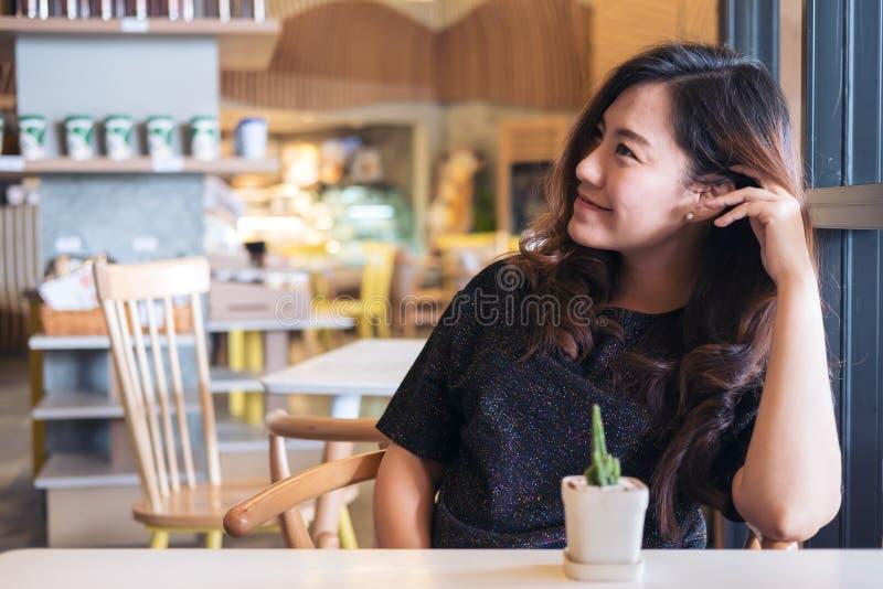 Imagen del retrato del primer de una mujer asiática hermosa sonriente con sentirse bien sentarse y la relajación en café con un p imagenes de archivo