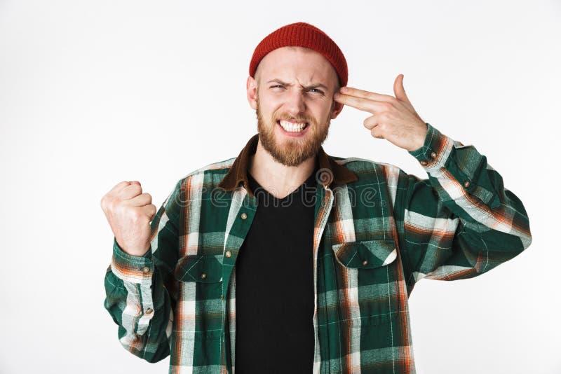 Imagen del sombrero descontento del individuo barbudo y de la camisa de tela escocesa que llevan que ponen dos fingeres en el tem fotos de archivo libres de regalías